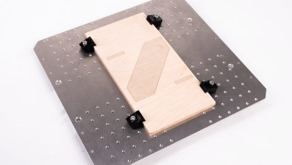 Plywood mounted on the CNC worktable using TopClamps.
